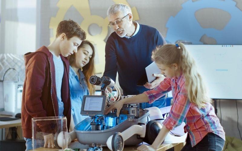 Insegnante con bambini e strumenti tecnologici per didattica innovativa